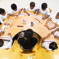 A pre-k class sits at round table with their teacher.