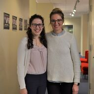 Two female alumni pose in a hallway.