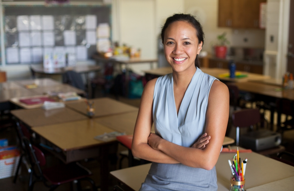 A smiling woman in her twenties, with long dark hair tied back, wearing a blue shirt and grey skirt, sitting on a desk in a classroom.