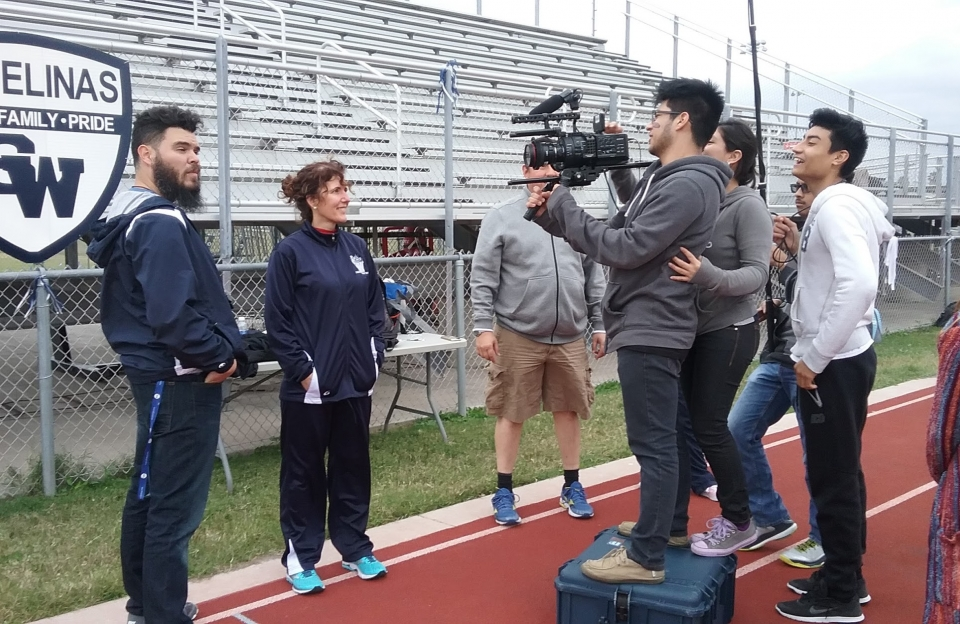 students filming a movie on a track