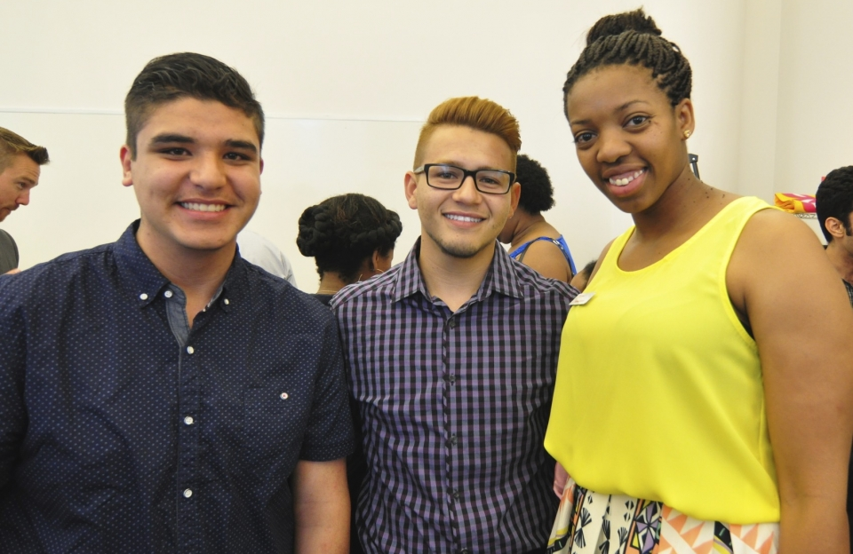 three people standing together smiling