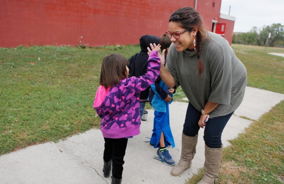 female teacher high fiving little girl outside school