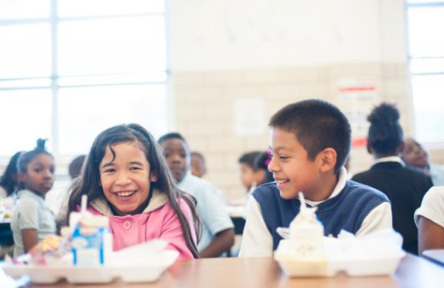 A young boy with a blue and white jacket smiling at a young girl with long brown hair and a pink jacket in a school lunch room.