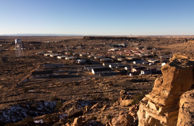 A view of a small desert town in daylight, looking down from a cliff.