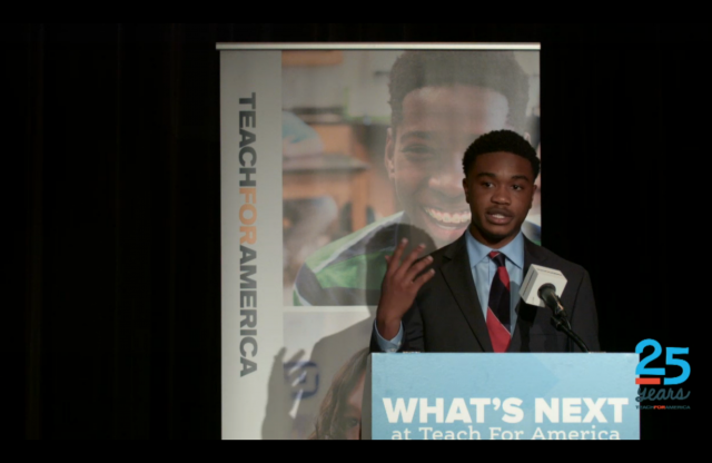 "A young man with curly black hair and a bearded chin addresses a crowd from a blue podium in front of a ""teach for america"" poster."