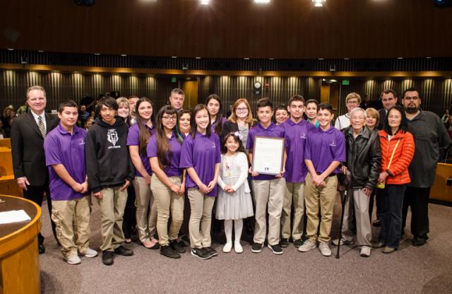 A large group of students in purple polo shirts stand with their teachers and advisors, smiling after winning an award.