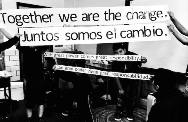 "A black and white shot of kids in a classroom holding white banners with the text ""Together we are the change"" and ""with great power comes great responsibility"" in both English and Spanish."