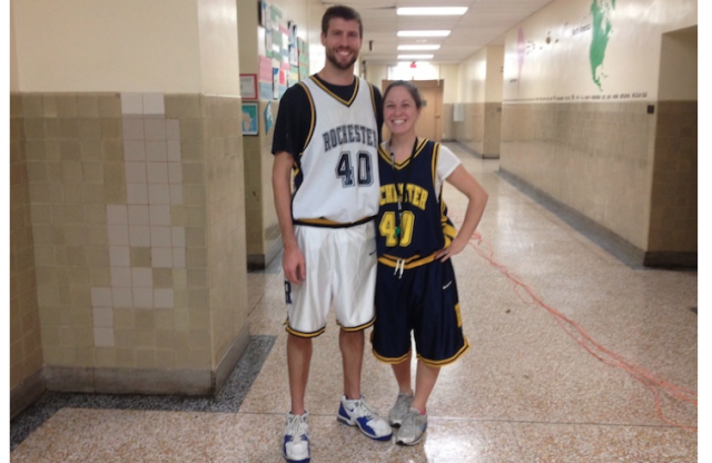 A tall young man with short blond hair in a white basketball uniform standing in a school hallway with his arm around a short young woman with brown hair tied up, wearing a dark blue basketball uniform.