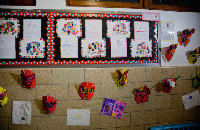 A shot of a wall in a school hallway covered with art projects, including a large number of multicolored masks.