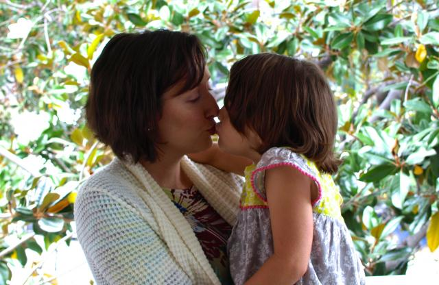A middle-aged woman with chin-length red hair and a white blazer kissing her daughter under the canopy of a tree.