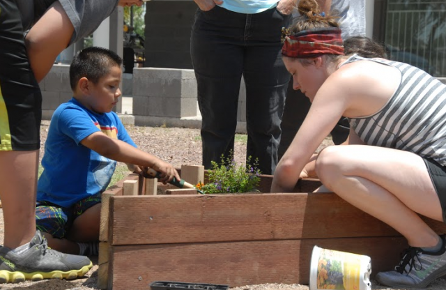 A young woman with brown hair tied up helps an elementary school-aged boy in a blue shirt planting herbs in a triangular wooden garden planter.