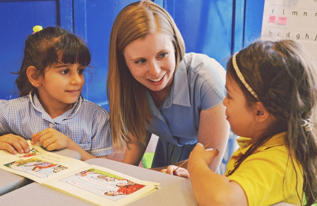 A young female teacher with long straight blonde hair and a blue dress leans down between two elementary school girls to help them practice their reading.
