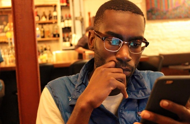 A young man with buzzed brown hair and red framed glasses sits in a coffee shop looking at his phone, with one hand up to his chin in a thinking pose.