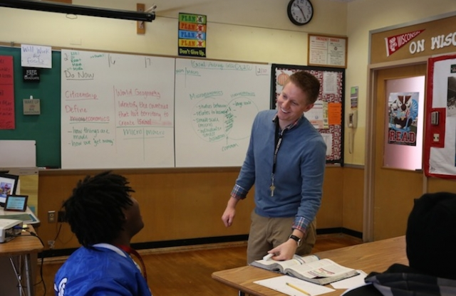 A young male teacher wearing a plaid shirt and a blue sweater at the front of a classroom, speaking to a middle-school boy with spiked braided brown hair.