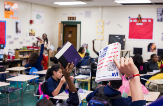 A shot of a middle-school classroom in which students are holding their books up, while a young female teacher looks on in the background.