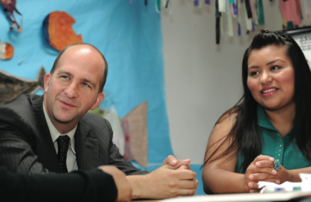 A middle-aged man with a bald head wearing a black suit and a young woman with long curly brown hair and a green dress sit at a classroom table listening to a question.