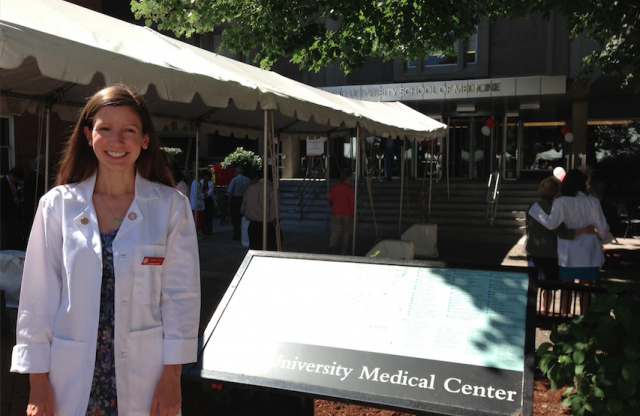 "A young woman with long straight brown hair wearing a lab coat stands smiling by a sign reading ""university medical center."""
