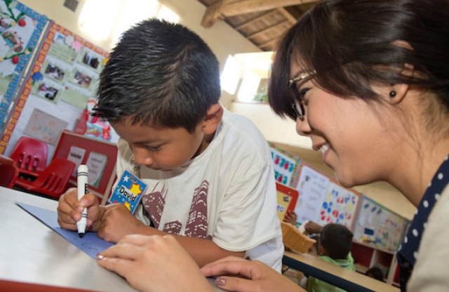 A young female teacher with straight dark brown hair and wire frame glasses smiling as she leans over an elementary student deeply engaged in using a marker for coloring.