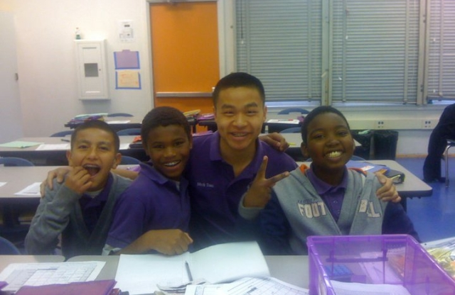 A shot of five middle-school students grouped together in a classroom, smiling.