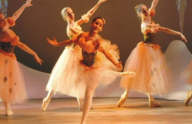 A young ballerina with long straight brown hair dancing on a stage, with four other dancers posing in the background behind her.
