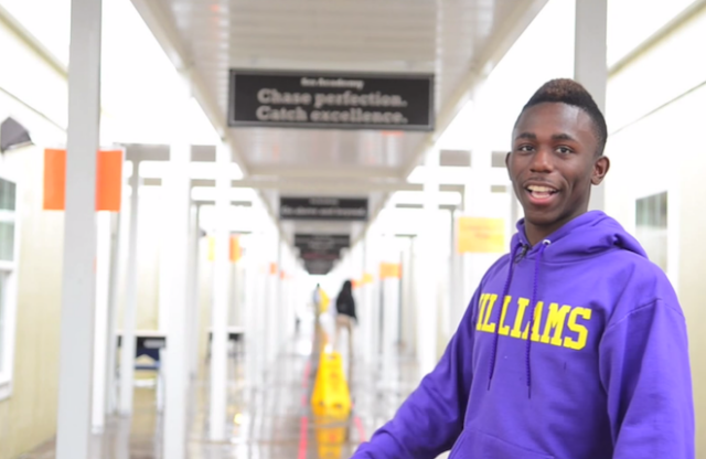 A young man with close-cut black hair and a purple hoodie stands smiling in a school hallway.