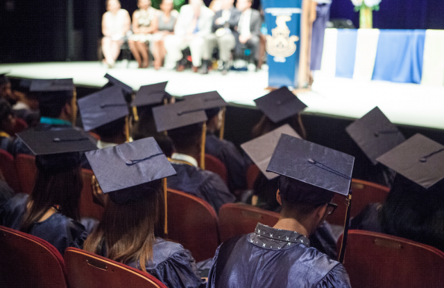 A room full of graduating students wearing mortarboards, with speakers on a brightly lit stage in the background.
