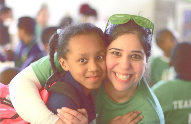 A young female teacher with a green shirt and sunglasses smiling as she embraces an elementary-school aged girl with brown hair in pigtails.