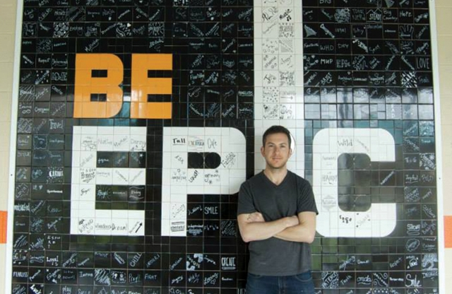 "A young man with short brown hair and a black shirt stands smiling, arms crossed, leaning against a tile background reading ""be epic""."