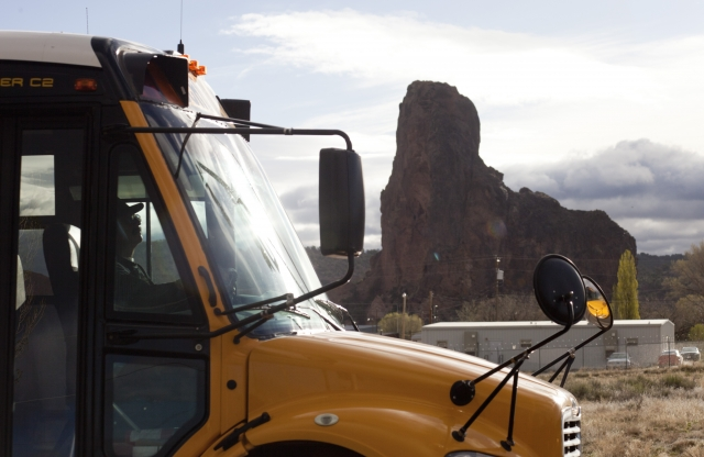 A yellow school bus, with a tall rocky mountain visible in the background.