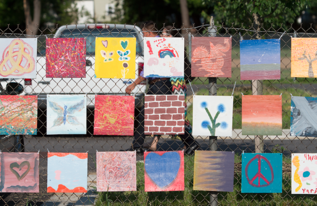 A chain-link fence with many square pieces of children s' art.