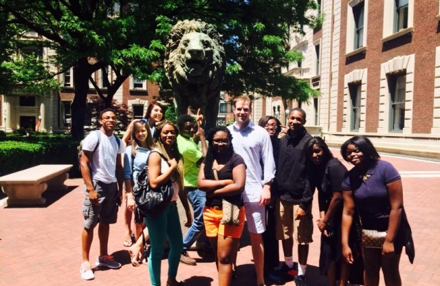 A group of high school students and a young male teacher with blond hair smiling in front of a statue of a lion.