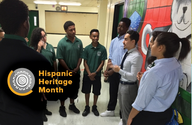 "A young male teacher with brown hair and a goatee speaks to a group of middle school students in a hallway, in front of a painted wall, with yellow text reading ""Hispanic Heritage Month."""