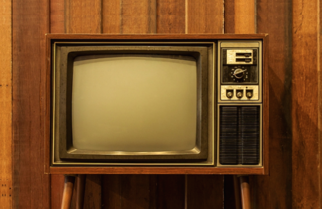 An old television sitting on a wood table, in front of a wood panel wall.