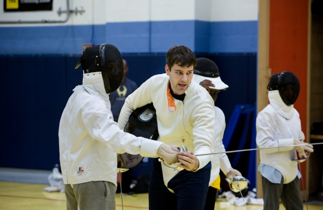 A young man with short brown hair teaching a middle-school aged student how to practice fencing.