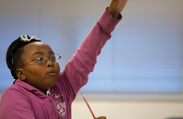 An elementary school girl with black curly braided hair and a pink sweater raises her hand excitedly in the classroom.