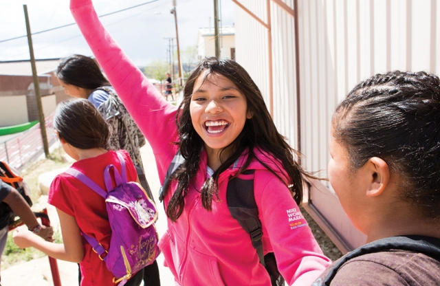 A middle-school aged girl with long straight hair and a bright pink jacket smiling outdoors with her arm up, with a crowd of other students around her.