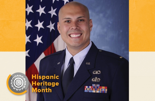 "Head shot of a middle-aged bald man in a military dress, smiling, wearing a uniform and medals, with an American flag in the background, with the words ""Hispanic Heritage Month"" below, in yellow."