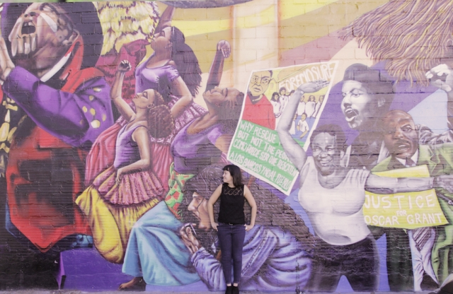 A young woman with straight black hair and a black shirt, leaning against a wall with a huge mural of Martin Luther King and his followers.