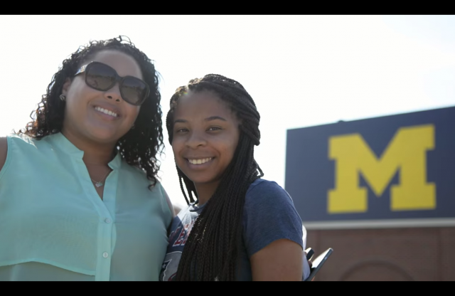 "A middle-aged woman with curly brown hair, sunglasses and a blue blouse, and a young woman with long braided black hair smiling together in a stadium with a yellow ""M"" on a blue sign."