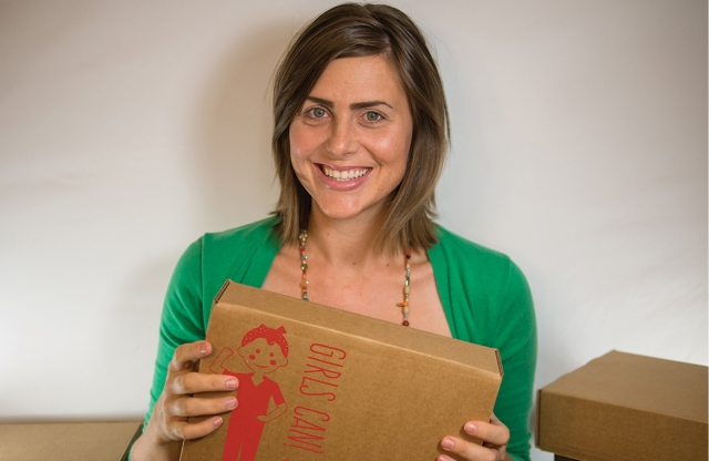 A young female teacher with shoulder-length light brown hair smiling, holding a brown box with a red logo on it.