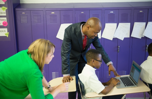 A middle-aged teacher with a shaved head and brown goatee helps a middle-school boy with a computer assignment in front of a background of purple lockers.