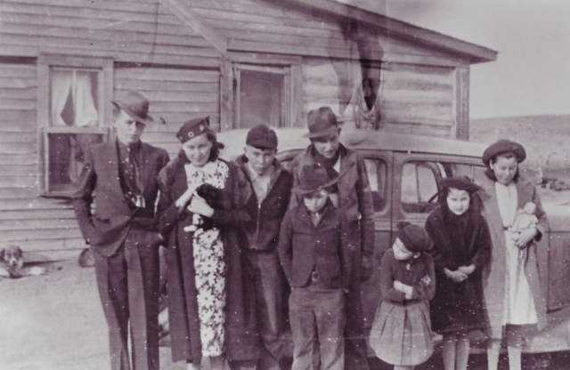 A very old photo of a family of ten posed in front of a wooden house and a car.