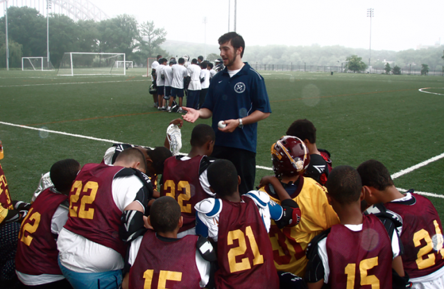 A young male teacher with short brown hair and a blue shirt gives an inspiring speech on the field to his football team, in red and yellow jerseys.