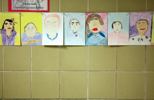 A yellow tiled wall with a row of elementary student self-portraits in crayon taped across.