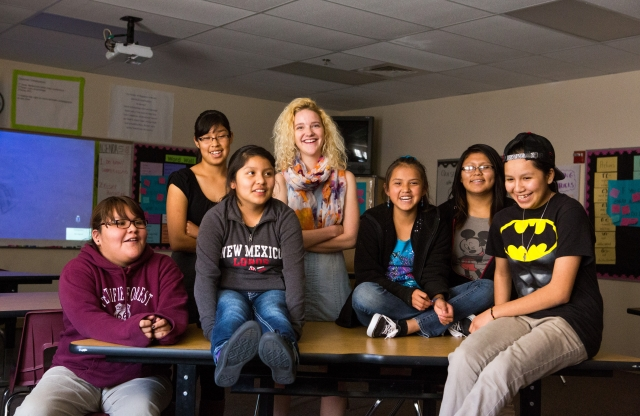 A young female teacher with shoulder-length curly bleach-blonde hair smiles among a group of smiling middle-school students in a classroom.