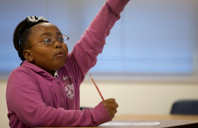 A middle-school girl with curly black hair tied up and a pink sweater energetically raising her hand in class.