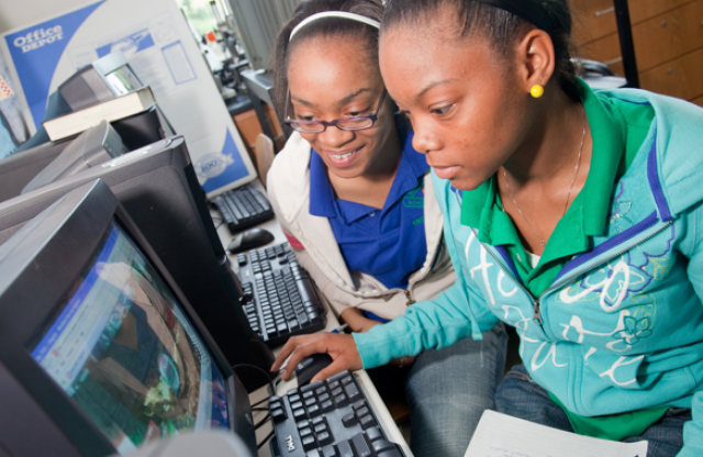 Two middle-school aged girls with curly brown hair happily working together at a computer.
