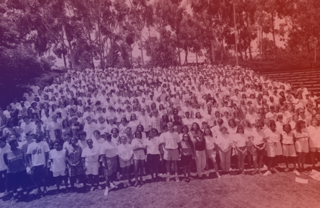 An overexposed photograph of hundreds of students, mostly in white, standing on bleachers, outside, in front of tall trees.