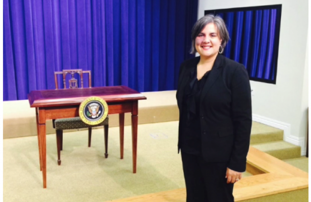 A middle aged woman with silver hair, wearing a black suit, standing next to a stage with a table with the emblem on the united states on it and a chair, in front of a blue curtain.