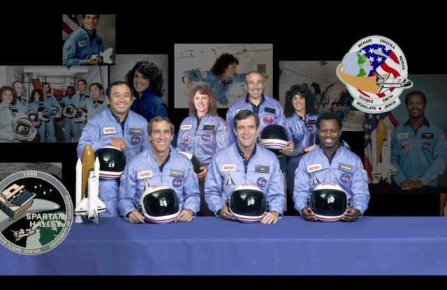 Group photo of five male and two female astronauts in front of a table with a blue cloth, and behind them are photos of the astronauts in various activities on a black background, with two space agency emblems.